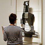 A woman wearing the perfect shirt in front of Picasso's guitar sculpture